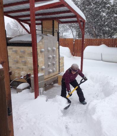 Nicole shoveling snow in front of her kiln.